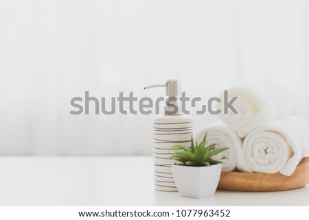 Ceramic soap, shampoo bottles and white cotton towels on white counter table inside a bright bathroom background. #1077963452