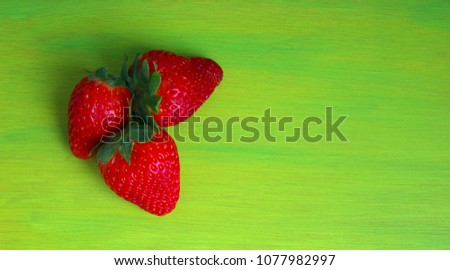 red strawberries isolated on a green background #1077982997