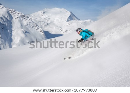Female freeride skier in the mountains off-piste #1077993809