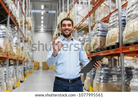 wholesale, logistic, business, export and people concept - happy man or manager with clipboard at warehouse showing ok hand sign #1077995561