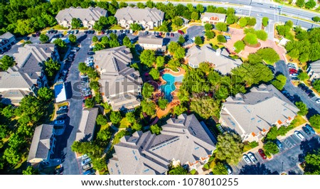 Curved modern swimming pool and bright lush green trees surrounding cozy new development suburb apartment complex townhomes - aerial drone view - Round Rock , Texas , USA #1078010255