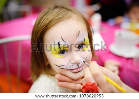 """Face painting for cute little gorl during kids merriment. Face paint for """"Animals"""" theme on birthday party. Preschooler kids celebrating party in entertainment center"""