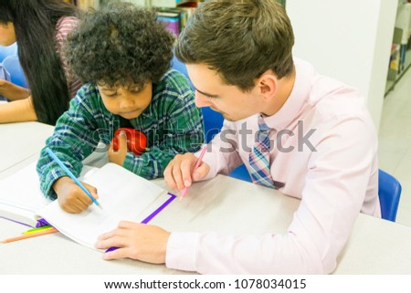 man teacher and kid student learn with book at bookshelf background #1078034015