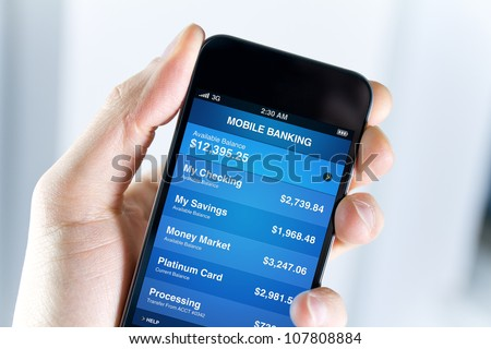 A man holding mobile smart phone with mobile banking application on a screen. Closeup shot. #107808884