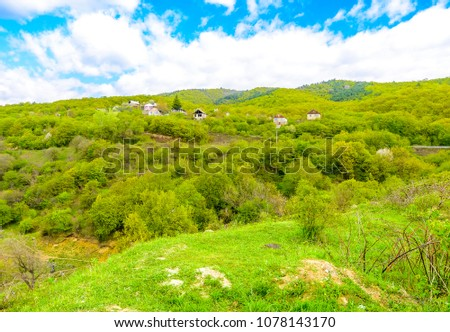 Beautiful pristine mountain village nestled against mountains and spring greens with blue skies and puffy clouds. #1078143170
