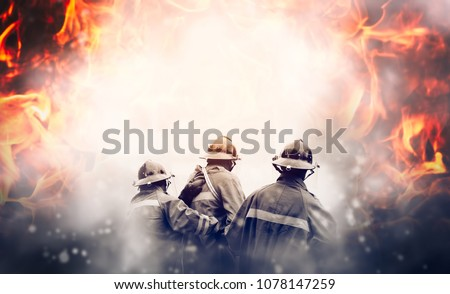 Group of firefighters fighting a fire, They are in the midst of fire and smoke.