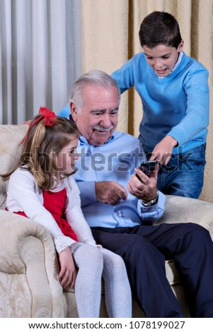 A grandfather is sitting with his grandchildren, learning to use the mobile phone #1078199027