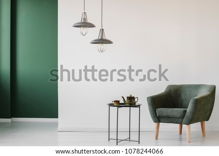 Upholstered, dark armchair and an industrial side table with a tea kettle and cup in a minimalist living room interior with a green corner #1078244066