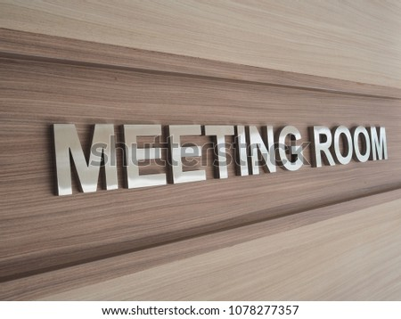 Meeting room sign hanging on the wall wood background texture.