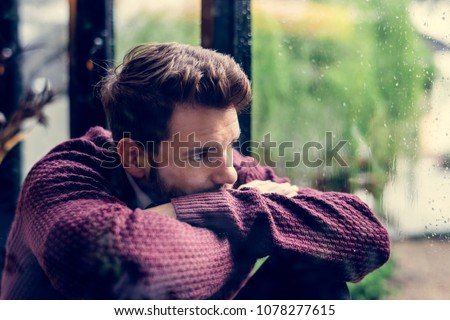 Thoughtful man looking out the window Royalty-Free Stock Photo #1078277615