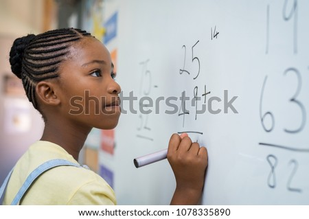 Portrait of african girl writing solution of sums on white board at school. Black schoolgirl solving addition sum on white board with marker pen. School child thinking while doing mathematics problem. #1078335890