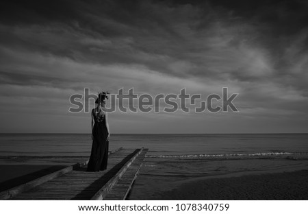 Beautiful woman in a dark luxury dress with big flower crown on head stand on a wooden pier. Dark clouds and sea on background. Black and white #1078340759