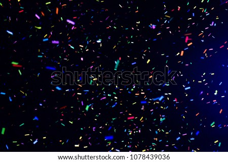 Thousands of confetti fired on air during a festival at night. Image ideal for backgrounds. Multicolor are the confetti in the picture. The sky as background is black. Cold tonality
