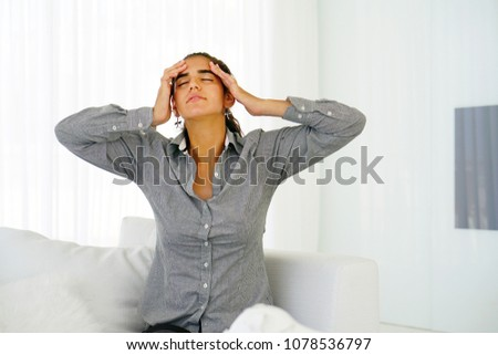 Young woman suffering from headache migraine pain at home on sofa. Health problem, stress and depression. Female holds head with hand. Concept of health. #1078536797