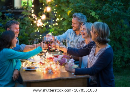 One summer evening, friends in their forties gathered around a table in the garden lit by luminous garlands. They toast with their glasses of wine Royalty-Free Stock Photo #1078551053