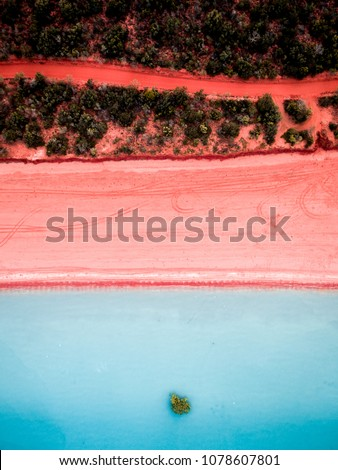 Aerial view of a pink sand beach and red dirt road next to Roebuck Bay in Broome, Western Australia. #1078607801