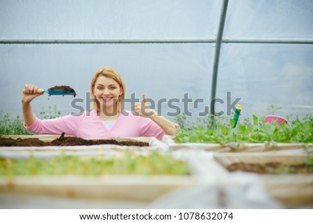 Smiling florist in pink cardigan standing behind boxes with plants in greenhouse. Blond woman holding small gardening spade full of soil in her hand. #1078632074