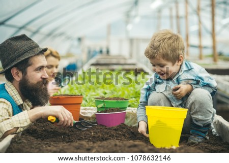 Smiling kid playing with family in greenhouse. Bearded man in blue vest, yellow shirt and hat looking at his son, mommy checking plants with magnifying glass. Eco gardening concept. #1078632146