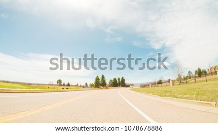 POV- Driving on paved road in suburban neighborhood in Colorado. #1078678886