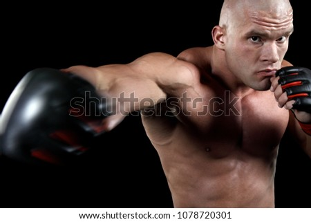 Powerful fighter punching in front of black background #1078720301