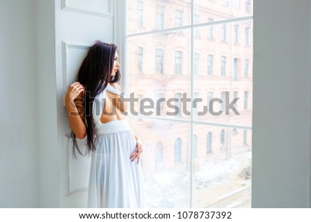Beautiful sexy girl in white dress by the window. romantic image. fashion indoor portrait of elegant sexy woman in luxurious  dress near the window #1078737392
