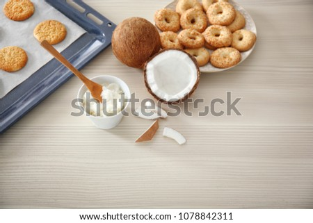 Bowl with coconut oil and cookies on wooden background #1078842311