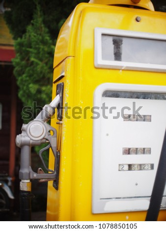 old vintage retro yellow gasoline benzine tank station standing unused as decorative element outdoor with blur background #1078850105