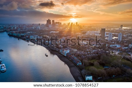 London, England - Panoramic aerial skyline view of east London at sunrise with skycrapers of Canary Wharf and beutiful colorful sky at background #1078854527
