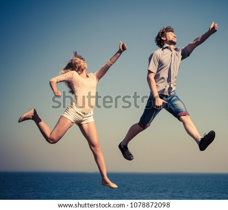Carefree young couple friends jumping by sea ocean water. Happy woman and man having fun. Summer happiness and freedom. #1078872098