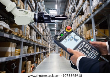 Engineer with teach pendant device. Programming robot with robotic arm in warehouse #1078895918
