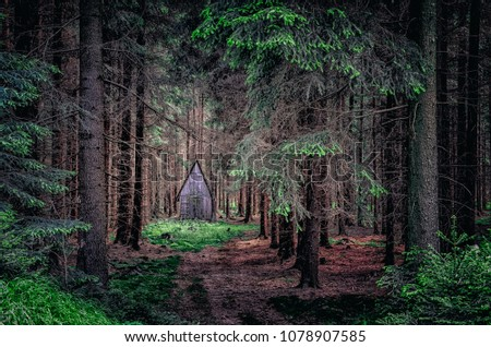 Dramatic dark landscape view of wooden cabin in the woods #1078907585