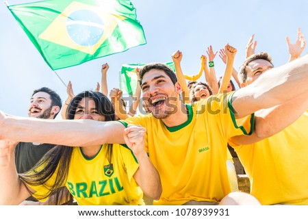 Brazilian supporters celebrating at stadium with flags. Group of fans and friends watching a match and cheering team Brazil. Sport and lifestyle concepts during international cup match #1078939931