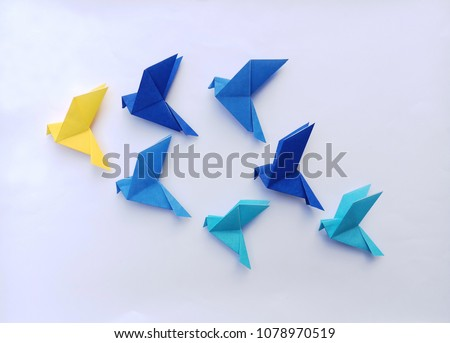 Seven blue origami  birds are flying leading by a yellow bird , isolated on white. #1078970519