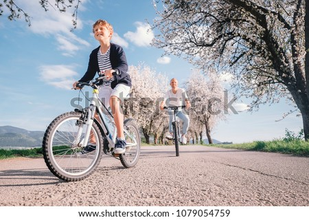 Father and son have a fun active leisure together - ride bicycles on country road #1079054759