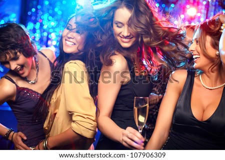 Cheerful girls living it up on the dance floor Royalty-Free Stock Photo #107906309