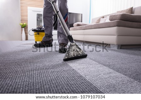 Low Section Of A Person Cleaning The Carpet With Vacuum Cleaner In Living Room #1079107034