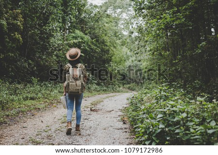 traveller women walking on road in the forest #1079172986