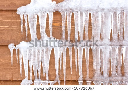 Icicles hang from a wood cabin on a chilly winter day Royalty-Free Stock Photo #107926067