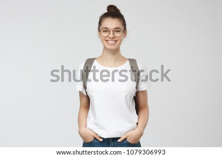 Indoor picture of young good-looking teenage girl isolated on gray background in white casual T-shirt, wearing glasses and gray backpack and jeans, feeling relaxed and positive, willing to walk #1079306993