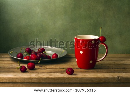 Still life with cherries and red cup #107936315