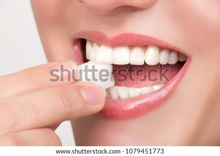 Beautiful woman's mouth with big white teeth bites on a white sugar cube #1079451773