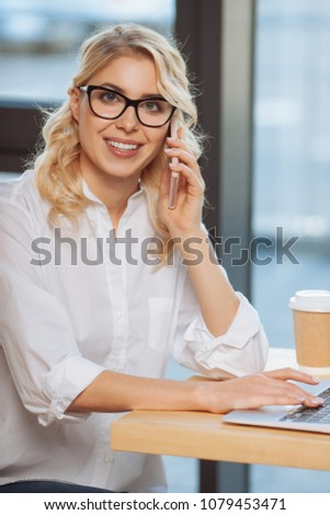 Business call. Cheerful nice positive businesswoman sitting at the table and making a business call while being involved in work #1079453471
