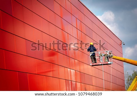 worker of Professional Facade Cleaning Services washing the red wall. Worker wearing safety harness washes wall facade at height on modern building in a crane. #1079468039