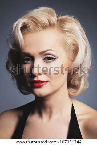 Pretty blond girl model like Marilyn Monroe in red dress with red lips on gray background
