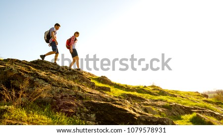 Couple of Young Happy Travelers Hiking with Backpacks on the Beautiful Rocky Trail at Warm Sunny Evening. Family Travel and Adventure Concept. #1079578931