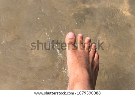 Man foot is walking in the sea with sand, water wave #1079590088