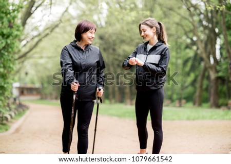 Young woman trainer showing elder woman how to walk with hiking sticks in the park #1079661542