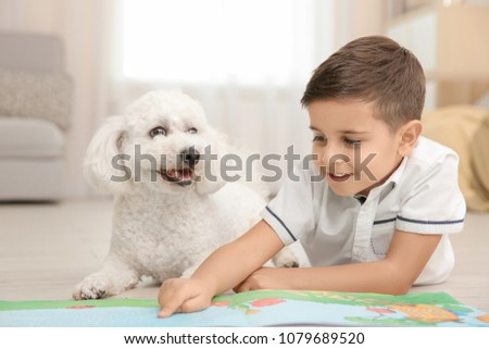 Little boy and bichon frise dog reading book at home #1079689520
