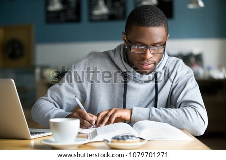 Focused millennial african american student in glasses making notes writing down information from book in cafe preparing for test or exam, young serious black man studying or working in coffee house #1079701271