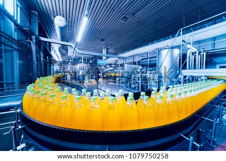 Beverage factory interior. Conveyor with bottles for juice or water. Modern equipments Royalty-Free Stock Photo #1079750258